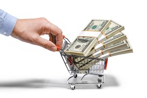 businessman's hand & steel grocery cart full of money stacks - i